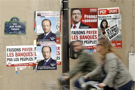 People ride bikes past campaign posters for candidates in the French presidential election which are posted on a wall in Paris March 29, 2012. REUTERS/Benoit Tessier