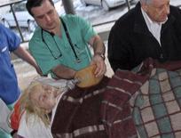 Медики рядом с жертвой изнасилования Оксаной Макар в госпитале в Донецке 16 марта 2012 года. 18-летняя девушка прожила 19 дней после того как была изнасилована и почти сожжена живьем в портовом Николаеве, где недовольство милицией, отпустившей обвиняемых на волю, вывело на улицы сотни горожан. REUTERS/Stringer