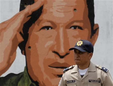 A police officer walks past a mural depicting Venezuelan President Hugo Chavez in Caracas March 26, 2012. REUTERS/Gil Montana