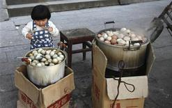 Menina olha para panela com ovos cozidos comuns ao lado de outra com ovos cozidos em urina de meninos em Dongyang, na província de Zhejiang. 26/03/2012  REUTERS/Aly Song