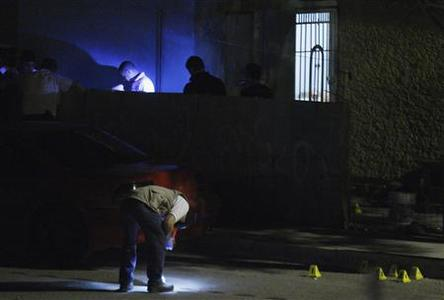 Police investigators inspect bullet shells at a crime scene in Ciudad Juarez March 28, 2012.Picture taken March 28, 2012. REUTERS/Jose Luis Gonzalez