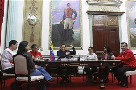 Venezuelan President Hugo Chavez (C) smiles as he gestures inside Miraflores Palace in Caracas March 29, 2012. REUTERS/Miraflores Palace/Handout