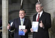 Canada's Prime Minister Stephen Harper and Finance Minister Jim Flaherty hold copies of the budget as they walk to the House of Commons to deliver the budget on Parliament Hill in Ottawa March 29, 2012. REUTERS/Patrick Doyle
