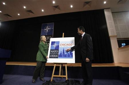 U.S. Secretary of State Hillary Clinton (L) and NATO Secretary General Anders Fogh Rasmussen unveil the logo of the Chicago summit meeting after a NATO foreign ministers meeting at the Alliance headquarters in Brussels December 8, 2011. REUTERS/Sebastien Pirlet