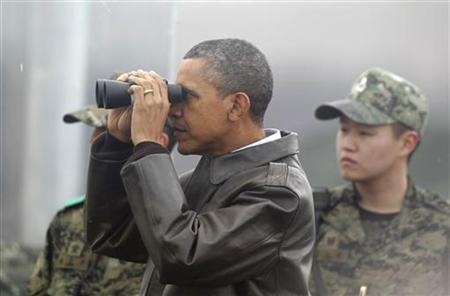 U.S. President Barack Obama looks through binoculars to see North Korea from Observation Post Ouellette during a visit to the truce village of Panmunjom in the demilitarised zone (DMZ) separating the two Koreas, north of Seoul March 25, 2012. REUTERS/Yuriko Nakao/Files