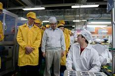 <p>Le directeur général d'Apple Tim Cook (à gauche) en visite dans une usine Foxconn, à Zhengzhou, où sont produits des iPhone. Apple dit travailler avec son principal sous-traitant, le chinois Foxconn, pour améliorer les conditions de travail et de salaires dans les usines qui fabriquent ses produits. /Photo prise le 28 mars 2012/REUTERS/Apple</p>