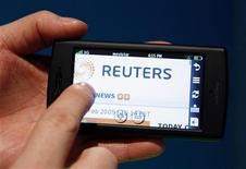 Мужчина держит смартфон с открытой веб-страничкой агентства Рейтер во время конгресса в Барселоне, 16 февраля 2009 года. Правительство Ирана приостановило действие аккредитации для сотрудников информационного агентства Рейтер в Тегеране после публикации видеосюжета об обучении женщин боевым искусствам, в котором содержалась ошибка. REUTERS/Albert Gea