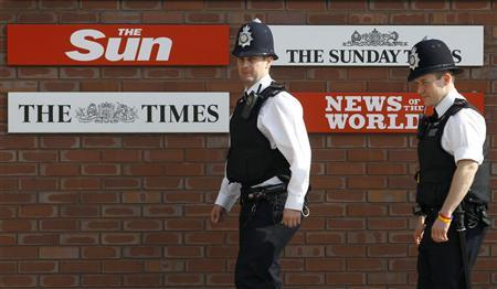 Police officers walk outside an entrance to News International in London in this July 10, 2011 file photo. REUTERS/Luke MacGregor/Files