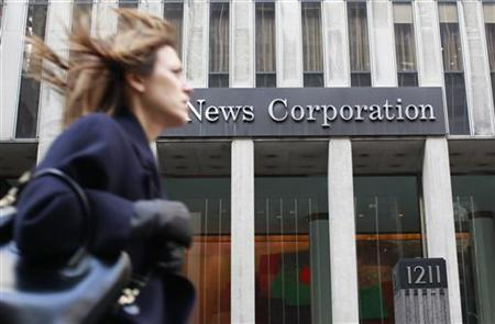 A woman walks past the NewsCorp building in New York February 8, 2012. REUTERS/Brendan McDermid/Files