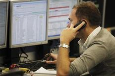 Трейдер разговаривает по телефону в торговом зале IG Index в Лондоне, 9 декабря 2011 года. Европейские рынки акций открылись ростом накануне встречи министров финансов еврозоны, на которой они, вероятно, договорятся об увеличении фонда помощи странам блока. REUTERS/Finbarr O'Reilly