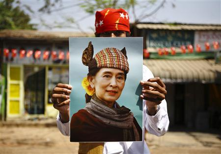 A supporter holds up a portrait of Myanmar pro-democracy leader Aung San Suu Kyi during an election campaign of the National League for Democracy (NLD) party in Yangon March 28, 2012. REUTERS/Staff