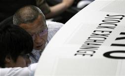 Трейдеры работают в торговом зале Токийской фондовой биржи, 9 августа 2011 года. Азиатские фондовые рынки, кроме Шанхая, снизились при закрытии торгов в пятницу, но выросли по итогам первого квартала. REUTERS/Kim Kyung-Hoon