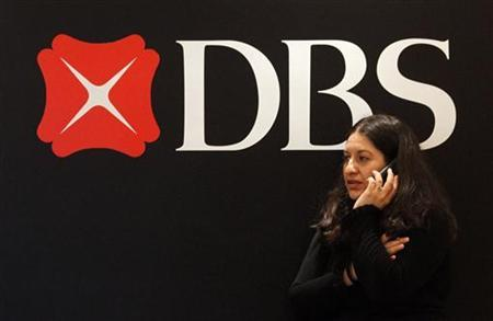 A woman speaks on a mobile phone while standing in front of a DBS Bank logo during a news conference in Singapore May 7, 2010. REUTERS/Vivek Prakash