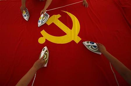 Workers use electric irons to smooth out a Communist Party of China flag on a table at the Beijing Jingong Red Flag factory, located on the outskirts of Beijing, June 28, 2011. REUTERS/David Gray/Files