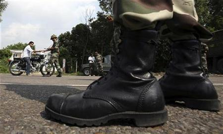 An Army soldier checks the identity papers of a motorist during a curfew in Jammu August 7, 2008. REUTERS/Amit Gupta/Files