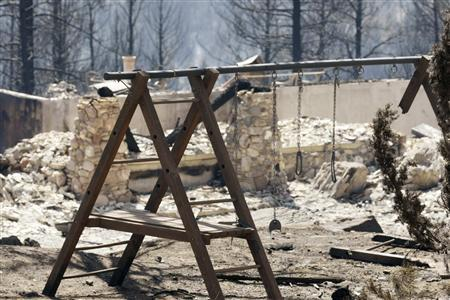 The swings are melted away from a child's swingset in front of a completely destroyed home on Kuehster Road near Conifer, Colorado March 28, 2012. REUTERS/Rick Wilking