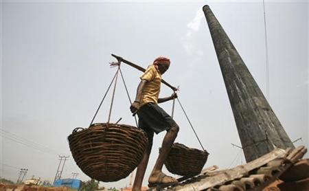 A worker carries coal in baskets at a wholesale coal shop on the outskirts of Agartala, capital of Tripura March 23, 2012. REUTERS/Jayanta Dey