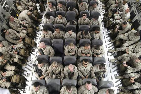 U.S. servicemen sit after boarding a transport plane before leaving for Afghanistan at the U.S. transit center at Manas airport near Bishkek, March 27, 2012. REUTERS/Vladimir Pirogov