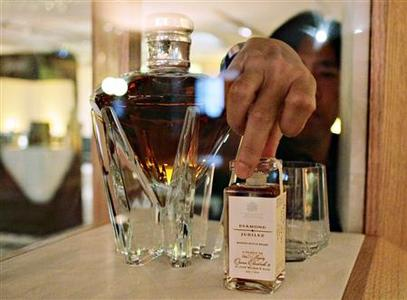 A staff positions a sampling bottle of the Diamond Jubilee whisky made by Johnnie Walker before an event featuring speciality wine and liquor by luxury travel retailer DFS Group at a hotel in Singapore March 31, 2012. The whisky made to mark the 60th year on the throne of Britain's Queen Elizabeth II is on sale in Singapore for a mere S$250,000 ($198,500) a bottle - and it may well find a buyer. REUTERS/Tim Chong
