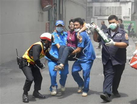Thai rescue workers and police evacuate a woman at the Lee Gardens Plaza Hotel in Hat Yai, Songkhla province, March 31, 2012. REUTERS/Stringer
