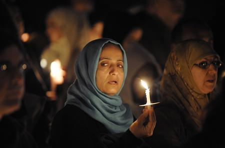 Mourners hold up candles at a candle light vigil held at a city park in Santee, California, for Shaima Alawadi, a 32-year-old Muslim woman who was beaten to death, March 30, 2012. Mourners gathered to pay respects for Iraqi-American Alawadi, who died after being severely beaten in her California home by a killer who left a threatening note that has prompted an investigation of the case as a possible hate crime. REUTERS/Denis Poroy