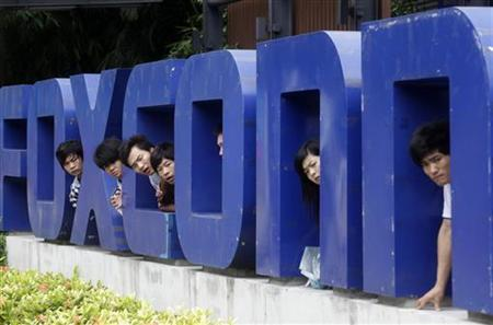 Workers look on from a Foxconn logo near the gate of a Foxconn factory in the township of Longhua, Guangdong province May 29, 2010. REUTERS/Stringer/Files