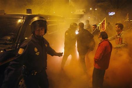 A truck (rear) is escorted by riot police officers as union picketers try to stop it at the entrance of Malaga's main food warehouse ''MercaMalaga'', at the start of a nationwide general strike in Malaga, southern Spain early March 29, 2012. Spanish unions hold a general strike on Thursday in a test of public patience with austerity a day before Prime Minister Mariano Rajoy announces a new round of deep budget cuts. REUTERS/Jon Nazca