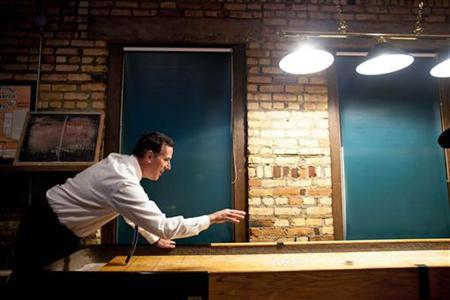 Republican presidential candidate and former U.S. Senator Rick Santorum plays a friendly game of shuffle board at Title Town Brewery in Green Bay, Wisconsin March 24, 2012. REUTERS/Darren Hauck