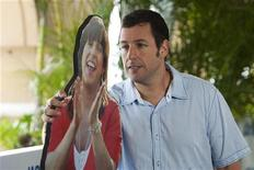 "U.S. actor Adam Sandler poses next to a cardboard cutout of his character during the film premiere of ""Jack and Jill"" in Cancun, July 10, 2011. REUTERS/Victor Ruiz Garcia"