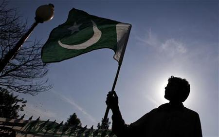 A supporter of the Pakistan Islamist party Pasban is silhouetted against the sun as he waves the national flag during a protest march towards the U.S. consulate in Karachi February 10, 2012. REUTERS/Akhtar Soomro