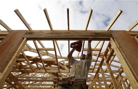 A tradesman uses a nail gun on the framework of a new house on the outskirts of Melbourne August 3, 2010. REUTERS/Mick Tsikas