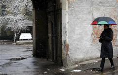 Женщина идет под зонтом по улице в Москве, 17 ноября 2009 года.  Рабочая неделя в Москве не принесет столичным жителям долгожданного весеннего потепления - по ночам все так же будут легкие морозы, а днями - облачность и осадки, прогнозируют синоптики. REUTERS/Denis Sinyakov