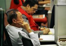 Трейдер следит за ходом торгов на бирже в Гонконге, 11 ноября 2009 года. Фондовые рынки Азии, кроме Гонконга, выросли в понедельник благодаря сильным производственным показателям Китая. REUTERS/Bobby Yip