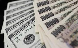 Американские доллары и японские иены, сфотографированные в Токио, 2 августа 2011 г. Иена отыграла потери к доллару, а более рискованные валюты, включая австралийский доллар, отошли от максимумов сессии по мере возобновления озабоченности инвесторов состоянием мировой экономики.  REUTERS/Yuriko Nakao