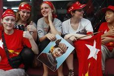 """Туристы празднуют победу лидера демократической оппозиции Мьянмы Аун Сан Су Чжи на довыборах в парламент, следя за ходом голосования по мониторам в штаб квартире ее партии в Янгоне 1 апреля 2012. Оппозиционная """"Национальная лига за демократию"""" во главе с лауреатом Нобелевской премии мира Аун Сан Су Чжи объявила о безоговорочной победе в борьбе за остаток мест в парламенте Мьянмы (Бирмы), где год назад сложила полномочия правившая 49 лет военная хунта. REUTERS/Soe Zeya Tun"""