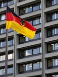 Немецкий флаг перед зданием Бундесбанка во Франкфурте-на-Майне, 2 мая 2011 года. Центробанк Германии сообщил в понедельник, что продолжит принимать все суверенные облигации еврозоны в качестве залога при операциях кредитования, опровергнув сообщения СМИ о том, что он якобы перестал принимать гособлигации периферийных стран блока, которые получают финансовую помощь от Евросоюза и Международного валютного фонда (МВФ).  REUTERS/Kai Pfaffenbach