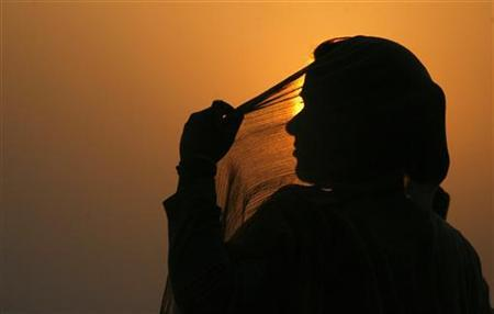 A woman adjusts her scarf as the sun sets over Kashmir's Dal Lake in Srinagar July 18, 2010. REUTERS/Danish Ismail/Files