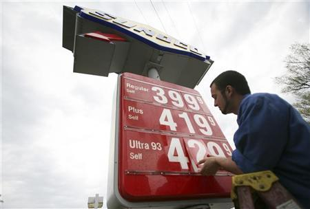 Employee Josh Watkins changes gas prices on a sign at a Sunoco station in Alexandria, Virginia April 12, 2011. REUTERS/Molly Riley
