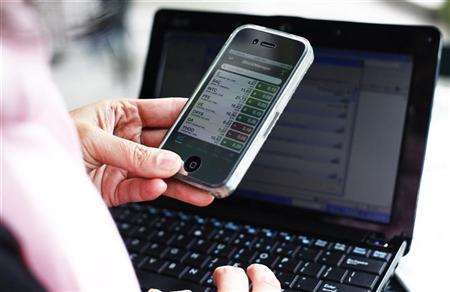 Amateur trader Yan Qin checks her smartphone for stock reports in New York December 7, 2010.  REUTERS/Shannon Stapleton