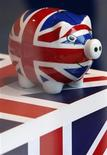 Хрюшка-копилка, раскрашенная в цвета британского флага, стоит в магазине в Лондоне, 24 марта 2010 года. Британская экономика покажет скромное восстановление по итогам первых трех месяцев 2012 года благодаря сильному зарубежному спросу, хотя страна по-прежнему сталкивается с трудностями на пути к здоровому росту, заявила во вторник британская Торговая палата.  REUTERS/Darrin Zammit Lupi