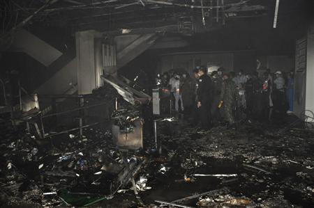 Thai security personnel investigate the site of a fire, which was caused by an explosion, at Lee Gardens Plaza hotel in Hat Yai district, Songkhla province, March 31, 2012. REUTERS/Stringer