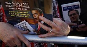 """Посетитель мероприятия в поддержку кандидата от республиканцев в президенты США Митта Ромни в Джексонвилле держит листовку с изображением президента Барака Обамы 26 января 2012 года. Комиссия по срочной биржевой торговле (CFTC) отклонила в понедельник предложение запустить опционные контракты на итоги президентских выборов США, поскольку такая """"игра"""" не отвечает общественным интересам. REUTERS/Brian Snyder"""