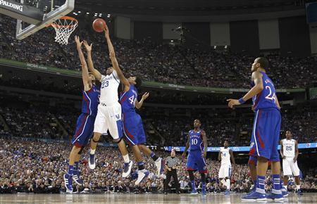 Kentucky Wildcats forward Anthony Davis (23) drives to the net between Kansas Jayhawks center Jeff Withey (L) and forward Kevin Young during the first half of their men's NCAA Final Four championship college basketball game in New Orleans, Louisiana, April 2, 2012. REUTERS/Jeff Haynes