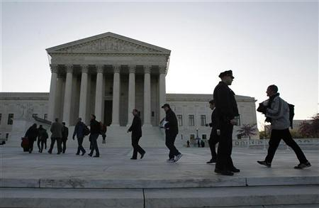 Members of the public who received tickets to watch the second day of legal arguments over the Affordable Care Act march into the Supreme Court in Washington, March 27, 2012. REUTERS/Jason Reed