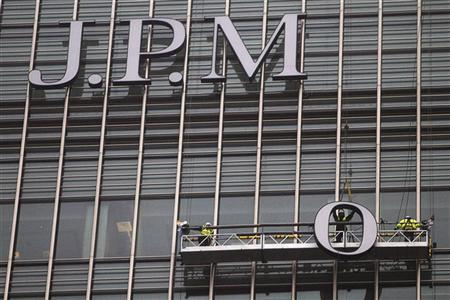 Workers erect a sign for JPMorgan investment bank at Canary Wharf in London December 21, 2011. REUTERS/Finbarr O'Reilly