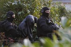 Diez supuestos islamistas fueron detenidos en la madrugada del miércoles en una operación policial en toda Francia como parte de las medidas ordenadas por el presidente Nicolas Sarkozy, después de que el mes pasado siete personas fueran asesinadas en unos ataques inspirados por Al Qaeda. Imagen de unos agentes enmascarados escoltando a un detenido en Coueron, cerca de Nantes, en la anterior operación policial, el 30 de marzo. REUTERS/Stephane Mahe