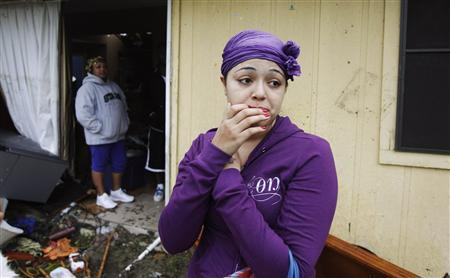 A resident looks at the damage caused by a tornado that ripped through the Dallas suburb of Lancaster, Texas, April 3, 2012. REUTERS/Tim Sharp