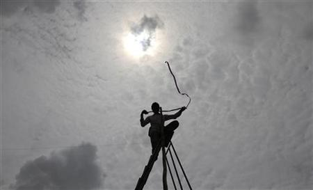 A man, standing on a ladder, is silhouetted by monsoon clouds while installing television cables in a residential area in Ahmedabad August 4, 2011. REUTERS/Amit Dave/Files