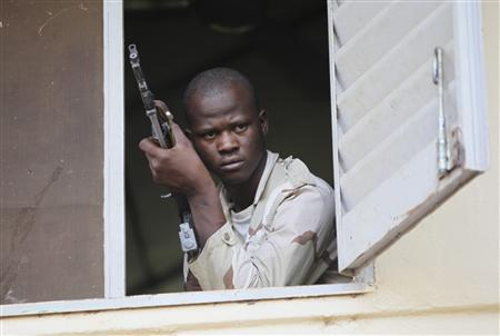 A Malian junta soldier holds a gun as he stands guard in the headquarters in Kati, outside Bamako April 3, 2012. REUTERS/Luc Gnago