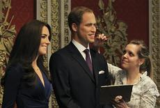 A gallery assistant poses with waxwork models of Britain's Prince William and his wife Catherine, Duchess of Cambridge during their unveiling at Madame Tussauds in London April 4, 2012. REUTERS/Olivia Harris